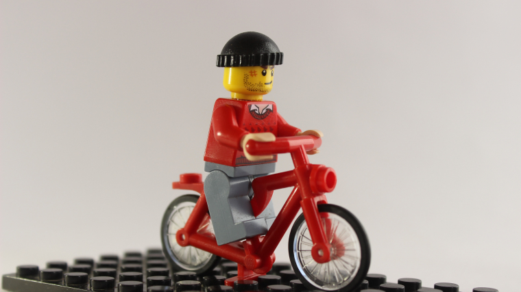 Lego figurine riding a red bicycle